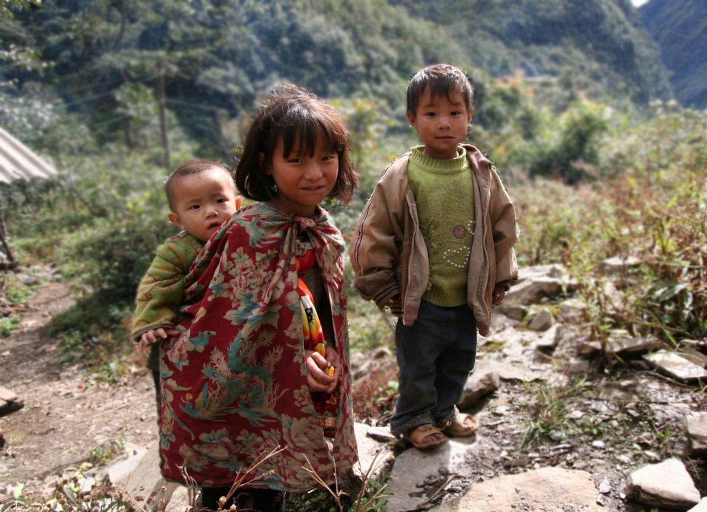 雲南省独龍のとても貧しい幼い兄弟 5歳に満たない姉が乳飲み子の子守をしている